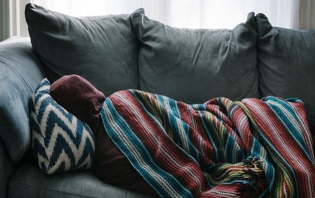 Person lying sick on a couch, wrapped in blankets