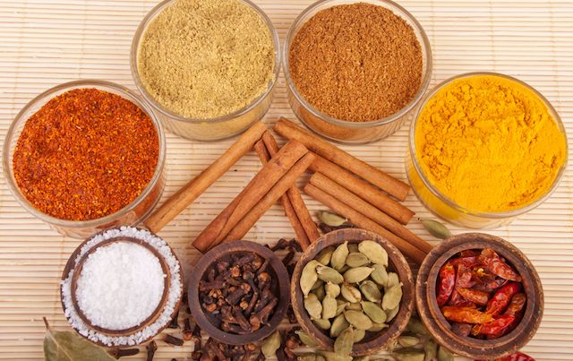 Arrangement of bowls and piles of spices and herbs.