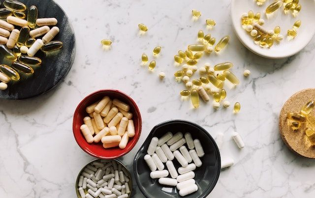 Many types of pills and capsules on a countertop and in several dishes and bowls