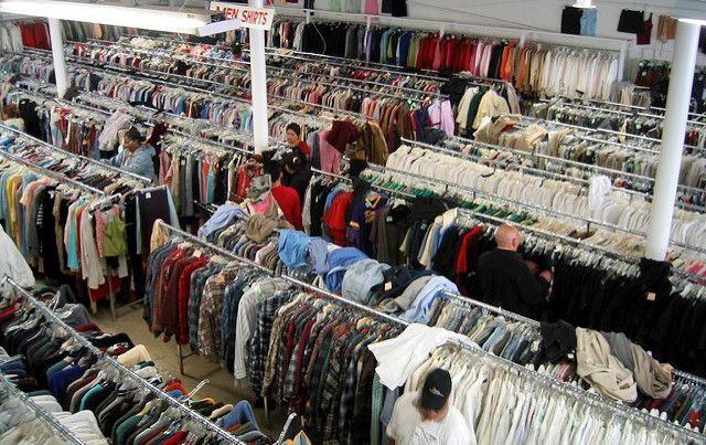Overhead shot of thrift store shoppers looking at racks of clothes.