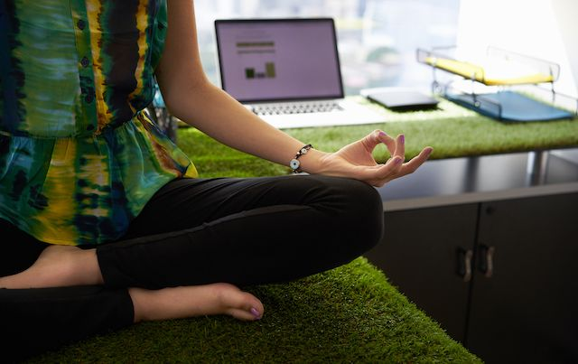Woman doing yoga pose sitting atop office desk.