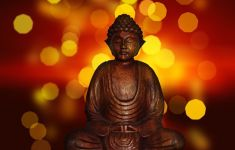 wooden Buddha statue in front of red and yellow lights