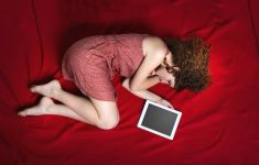 Woman lying in fetal position with iPad tablet