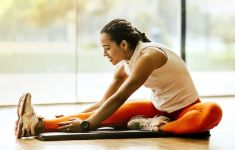 Woman in orange leotard doing seated yoga stretches in front of big window