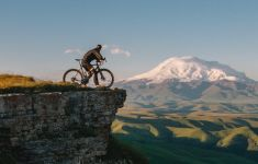 Bicyclist on cliff overlooking mountains and valley.