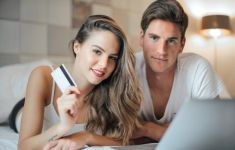Couple laying across bed with computer and credit card.