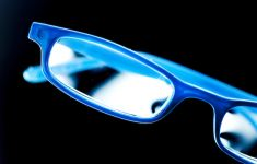 Bright blue eye glasses on black background.