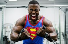 Intense weightlifter screaming while pumping iron in Superman shirt.
