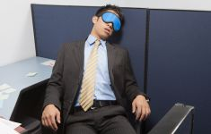 Man in business suit asleep in cubicle with sleep mask.