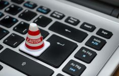 Tiny CAUTION cone on computer keyboard