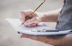 Close up of man's hands writing in journal while balancing cellphone.