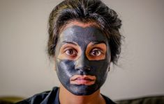 WOman with charcoal facial mask on her face