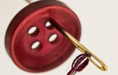 Close up of red button with needle and thread