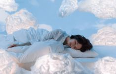Woman sleeping with decorative cloud shapes all around her.