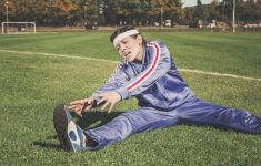 Comic image of woman stretching in the grass with look of agony.