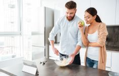 Attractive couple cooking together in kitchen looking at recipe on iPad