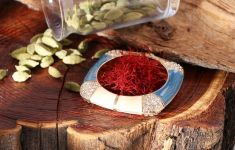 An ornate dish of saffron threads and spilled jar of cardamom pods
