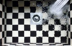 Water from faucet filling checkered sink and drain