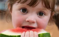 Close up of child biting into watermelon slice.