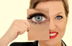 Woman holding photo of enlarged eye over her own eye.