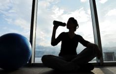 Silhouette of woman at gym drinking from sports bottle