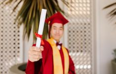 Young man in red cap and gown holds rolled diploma toward camera.