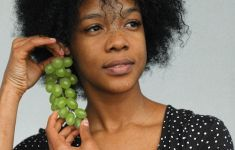 Woman looking to the side while holding bunch of green grapes.