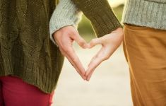 male and female hands make shape of heart