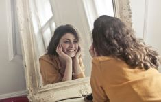 Woman smiling at her reflection in the mirror