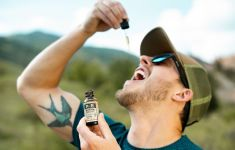 Man in sunglasses and hat with dropper of hemp oil