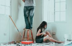 Man and woman repainting room with dropcloth, rollers, paint, etc.
