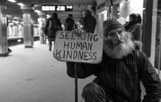 Homeless man in subway with sign says SEEKING HUMAN KINDNESS