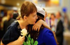 two women embrace as one holds a white rose