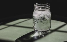 Mason jar of water against shadowy black background