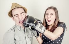 Woman playfully punching man with boxing gloves.