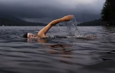 Open water swimmer in gray lake with mountains behind.
