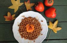 persimmon waffle on plate surrounded by autumn leaves and fruit