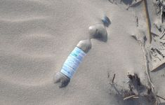 plastic water bottle pollution buried in sand
