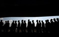 Silhouette of many people waiting in line.