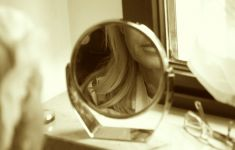 part of woman's face reflected in mirror