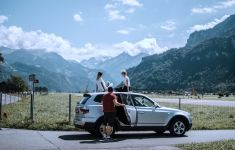 Three friends out of and standing up on car in front of countryside and mountains.