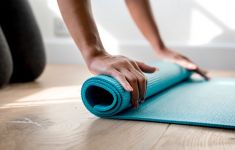 Close up of woman's hands rolling teal yoga mat.