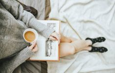 Torso down photo of wman reading in bed with cup of tea