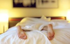 Bare feet of a sleeper sticking out form white sheets in bed.