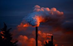 Smoke stack billowing exhaust into dramatic sunset sky