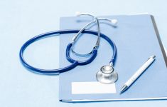 Stethoscope and pen on top of medical chart.