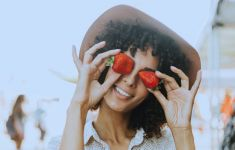Woman in hat holding strawberry up in front of her eyes