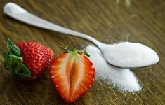 TEaspoon spilling sugar on wooden table next to cut strawberries