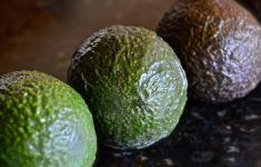 closeup on 3 avocados in moody light