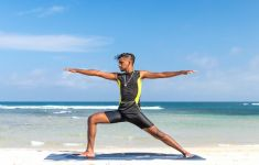 Man doing warrior yoga pose on the beach